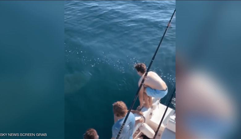 صورة مشهد يحبس الأنفاس لشابين يقفزان على ظهر سمكة قرش (فيديو)